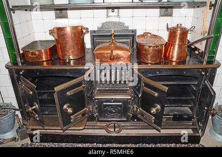 large. antique / vintage kitchen hearth with a variety of  copper pans and pots on it. - Stock Photo