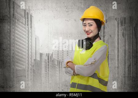 Asian business woman wearing yellow helmet smile - Stock Photo