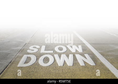 Big Slow Down sign on a footpath disappearing in white fog - Stock Photo