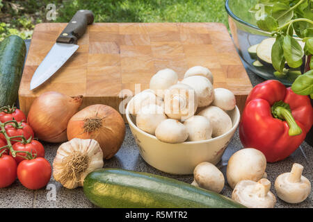 Wooden board, knife and various types of vegetables ready for preparing. - Stock Photo