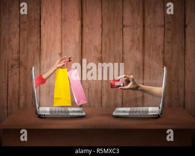 Hand out from computer carry shopping bag, the other show credit card - Stock Photo
