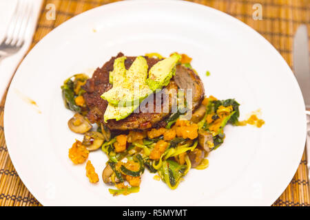 Homemade meal on white ceramic plate and textured table. Meal contains meat or meat substitute, leafy greens, mushrooms, sweet potatoes, avocado, and  - Stock Photo