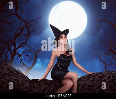 Young asian witch woman with hat standing around in a cemetery - Stock Photo