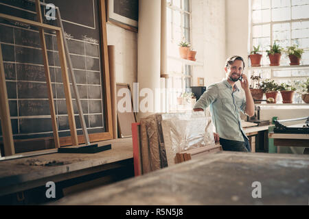 Positive business owner on phone in his workshop - Stock Photo