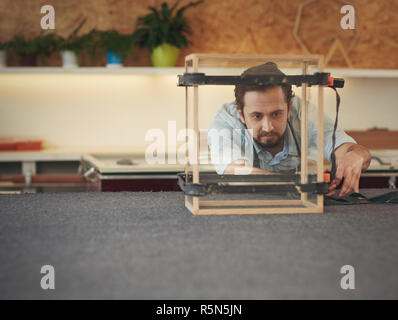 Craftsman inspecting the project he is manufacturing in his stud - Stock Photo