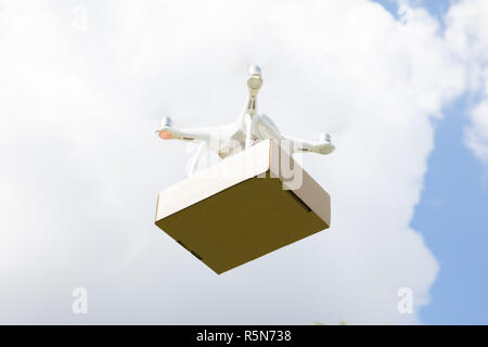 Drone delivering parcel against sky on sunny day - Stock Photo