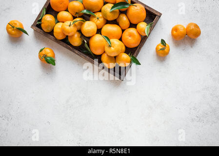 Tangerines (oranges, clementines, citrus fruits) with green leaves in box on white stone background, copy space. - Stock Photo