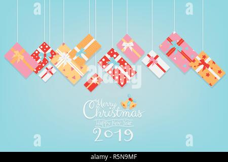 Colorful Christmas and Happy New Year 2019 banner design with gifts box hanging and calligraphy hand writing script on sweet green background with cop - Stock Photo