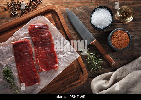 Raw calf flank beef on white cooking paper and wooden cutting board. Decorated with herbs, spices and chef's knife. Overhead view. - Stock Photo