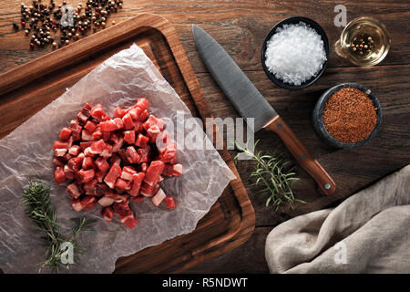 Raw calf meat chopped into small pieces on white cooking paper and wooden cutting board. Decorated with herbs, spices and chef's knife. Overhead view. - Stock Photo