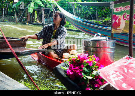 Beautiful Thai woman selling fresh coconut ice cream at the Damnoen Saduak Floating Market Thailand in Thailand or The Land of the Smiles. - Stock Photo