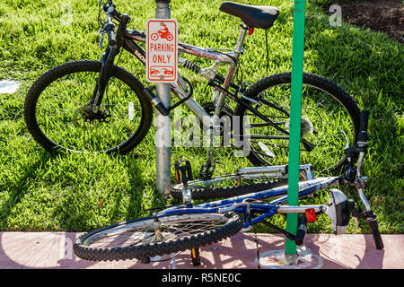 Miami Beach Florida Ocean Drive sidewalk parking meter warning sign motorcycle parking only bicycle locked to post prevent the - Stock Photo