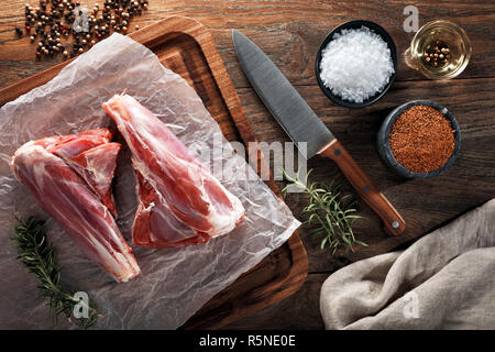 Raw lamb mutton leg drumstick on white cooking paper and wooden cutting board. Decorated with herbs, spices, chef's knife and napkin. Overhead view. - Stock Photo