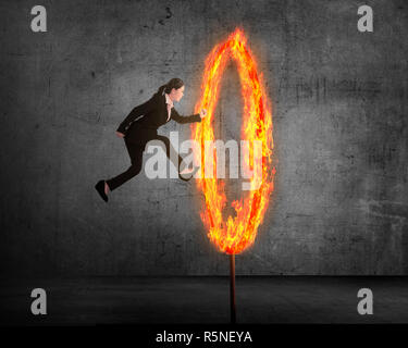 Asian business person jumping through ring of fire - Stock Photo