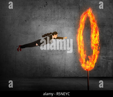 Asian business person flying through ring of fire - Stock Photo