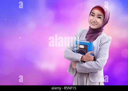 Beautiful asian woman wearing hijab holding koran - Stock Photo
