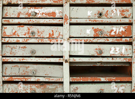 Block of very old damaged mailboxes in an apartment building. Many vintage painted postboxes in a row vintage background - Stock Photo