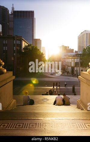 People sitting on stairs of Parliament House watching Melbourne henge, when the sun sets in line with CBD grid, Melbourne Australia - Stock Photo