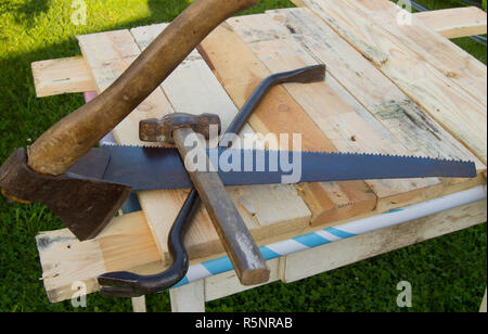 building tools hammer, axe, hacksaw frame, lie on the light boards in the garden - Stock Photo