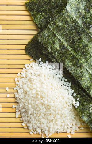 Green nori sheet and rice on bamboo mat. - Stock Photo