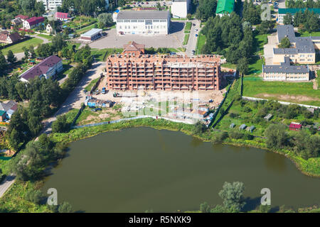 construction of apartment house in settlement - Stock Photo