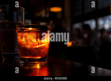 Cocktail close up on a bar counter. Drink is illuminated against a dark background with blurred people. - Stock Photo