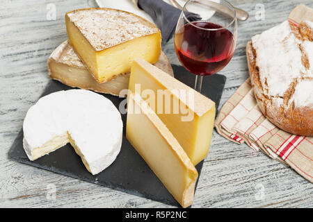 Different french cheeses with a glass of wine - Stock Photo