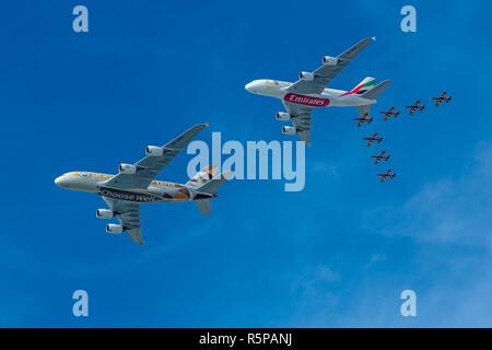 Abu Dhabi, United Arab Emirates. 2nd December 2018, UAE National Day fly past. Etihad and Emirates planes dwarf the Al Fursan aerobatic display team. Credit Elizabeth Coughlan/Alamy Live News. - Stock Photo