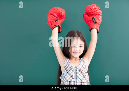 happy little girl with red boxing gloves stand before chalkboard - Stock Photo
