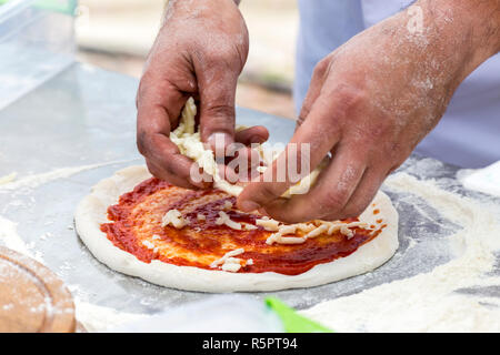 Putting cheese on a pizza with marinara sauce. - Stock Photo
