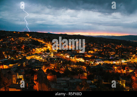 Top view. A small authentic city called Goreme in Cappadocia in Turkey in the evening. Dramatic night sky, sunset. Lightning above the town - Stock Photo