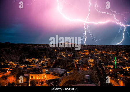 Lightning above the town of Goreme in Cappadocia in Turkey. Dramatic night sky. Beautiful view of the city. - Stock Photo