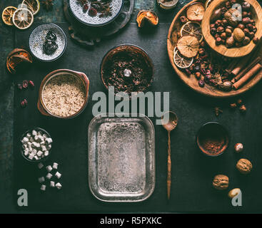 Preparation of homemade vegan chocolate truffle pralines with dried fruits and nuts mix, ingredients on dark background, top view. Healthy sweets. Ene