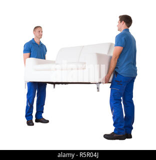 Young Movers Moving Sofa In New Home - Stock Photo