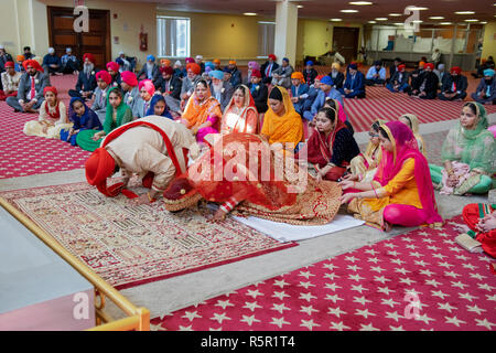 A Sikh bride and groom bowing during their wedding ceremony at a temple in Richmond Hill, Queens, New York - Stock Photo