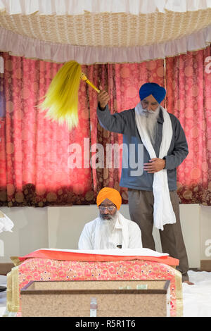 A Sikh priest reads from the holy prayer book while another devotee waves a yellow Chaur Sahib at a temple in South Richmond Hill, Queens, New York. - Stock Photo