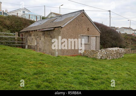 Old and long since abandoned publis toilet block at Ogmore by sea with delapidated slate roof and boarded up windows and doors. - Stock Photo