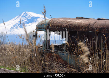 Abandoned and rusty old Soviet Russian bus in the middle of reeds and agriculture fields with Mt. Ararat on the background - Stock Photo