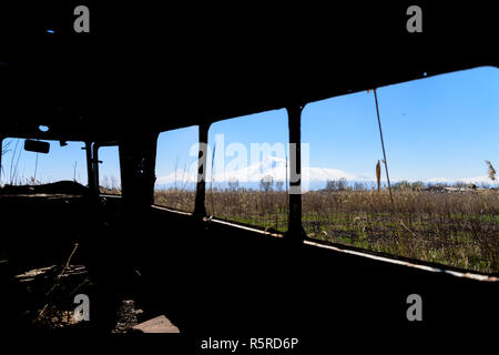 View from inside of an abandoned and rusty old Soviet Russian bus in the middle of reeds and agriculture field with scenic snow-topped Ararat mountain and clear blue sky on the background. - Stock Photo