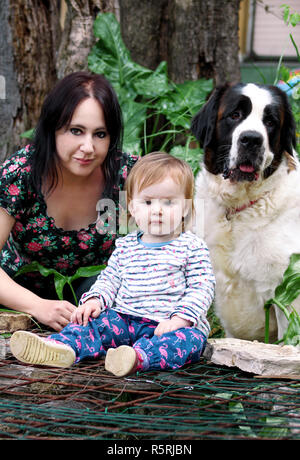 Family and love pets concept portrait with mother and baby girl is sitting and playing with dog in garden outdoors. Child and mom with St. Bernard dog - Stock Photo