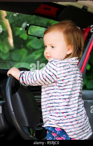 Child playing in car steering wheel. Cute little girl driving car. Child standing in big car. Close up young little female baby turns the steering. - Stock Photo