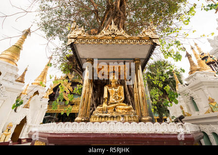 YANGON, MYANMAR - 16 NOVEMBER, 2018: Horizontal picture of Buddha statue under the Bodhi tree at Shwedagon Pagoda, located in Yangon, Myanmar - Stock Photo