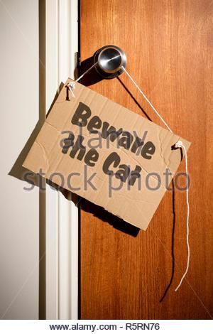 Beware the Cat written on a makeshift sign hanging on the door handle, Dorset, England. - Stock Photo