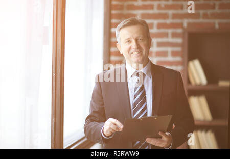 smiling senior businessman standing with document in office - Stock Photo