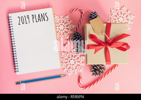 2019 New Year Plans, top view brown gift box, notebook and christmas decoration for new year on pink pastel color. - Stock Photo