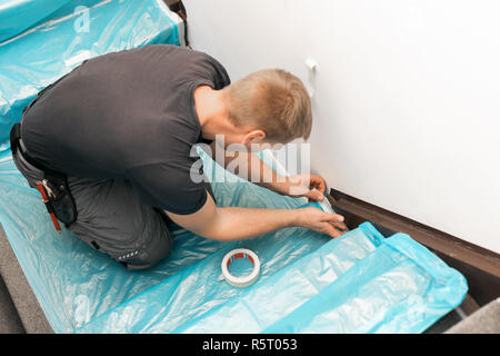 worker covering stairs carpet with masking film before home improvement works - Stock Photo
