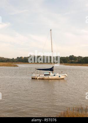 single private boat moored in river high tide landscape scene - Stock Photo