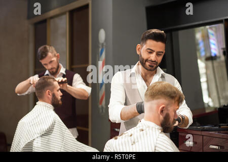 View from side of professional barber servicing male client sitting in chair in barbershop. Stylish hairdresser in uniform and protective gloves cutting hair. Concept of hairstyling and shaving. - Stock Photo