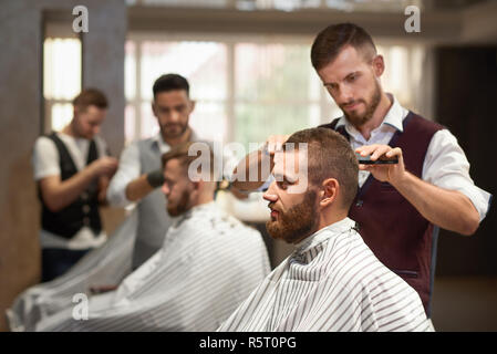 Side view of process of hairstyling in barber shop. Young bearded customer sitting in chair, looking at mirror and getting haircut. Professional hairdresser in uniform keeping scissors and razor. - Stock Photo