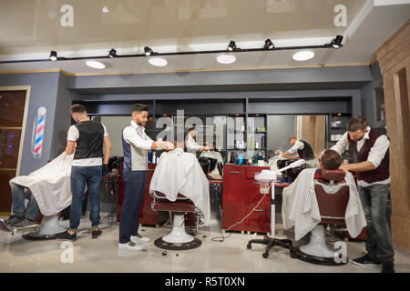 View from back of working process in vintage barber shop. Qualified hairstylists in white shirts and waistcoats shaving beard with razors and doing trendy haircuts. Concept of hairdressing.  - Stock Photo
